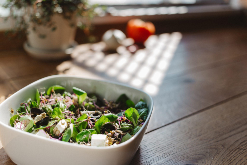 A bowl of salad on a wooden table