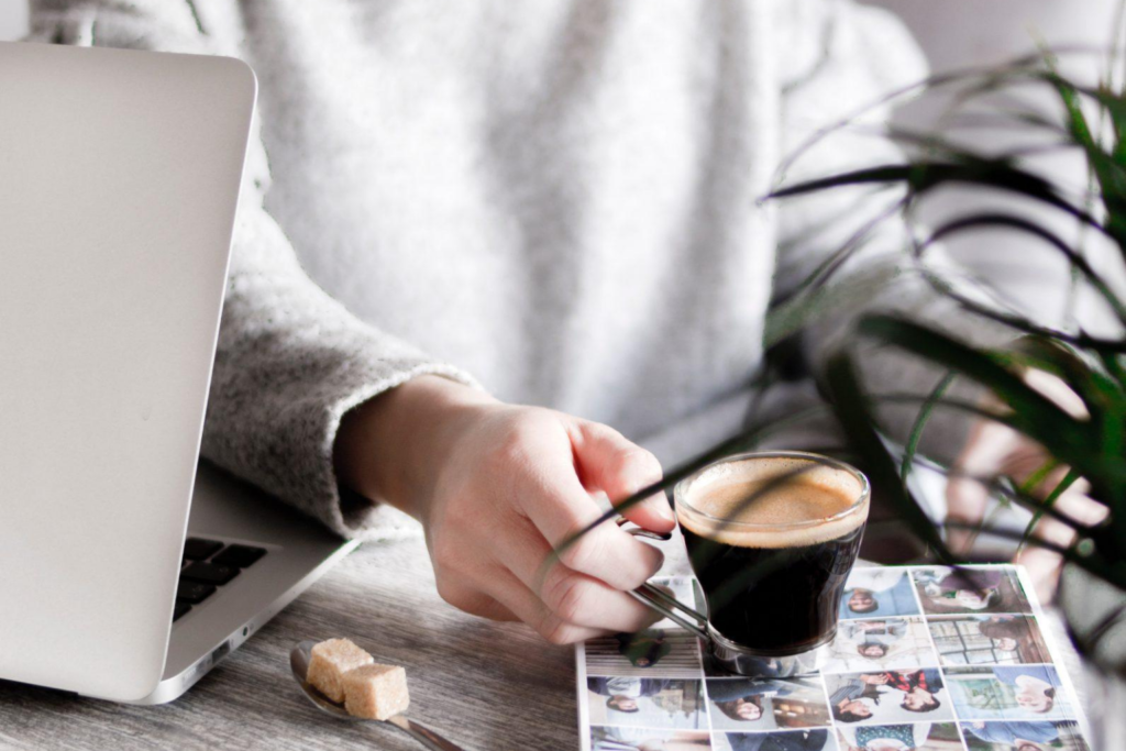 A woman holding a cup of coffee next to her laptop