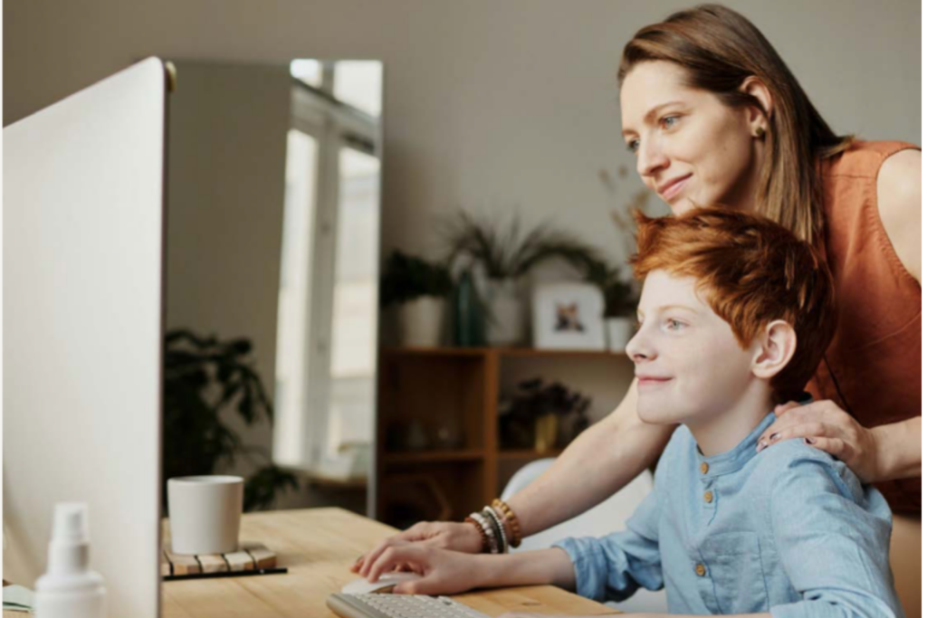 A mother and son on a computer together