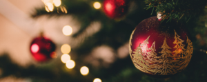 Celebrate this festive season with Ten: a red and gold bauble on a christmas tree