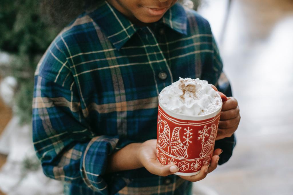 A young boy enjoying a hot chocolate