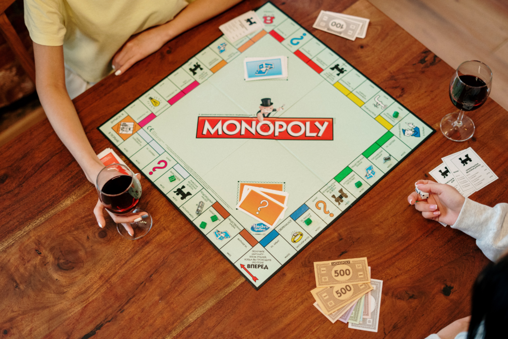 A game of Monopoly being played on a kitchen table