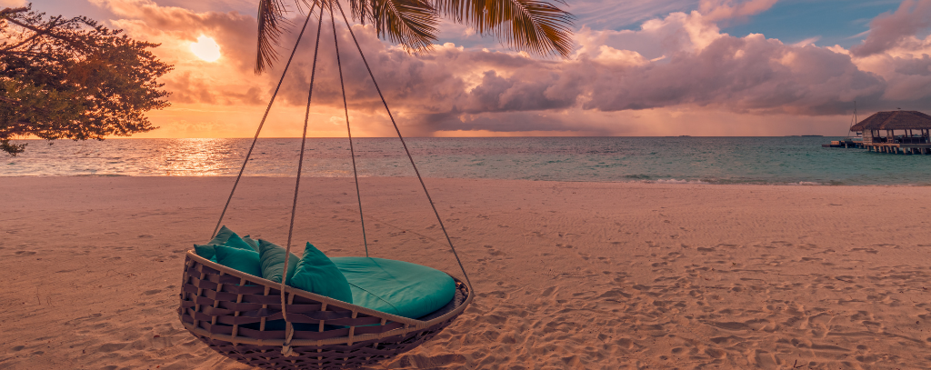 A swing chair overlooking the sea at sunset