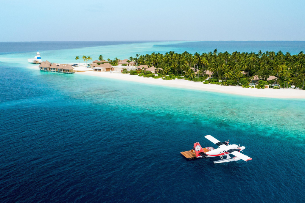 Travel inspiration: a sea plane next to a white sandy beach on the Maldives