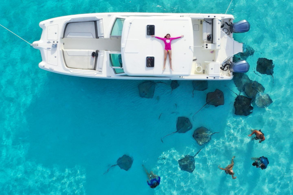 Travel inspiration: a girl in a pink top lying on a boat surrounded by stingrays on Grand Cayman