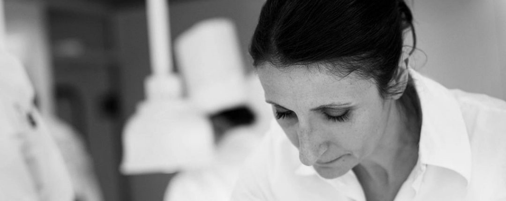 A black & white photo of Anne-Sophie Pic plating up using tweezers